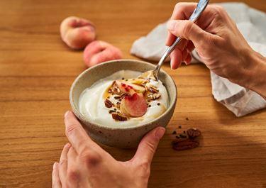 Arla® Skyr Bowl mit Pfirsich, Pekannüssen, Ahornsirup und Kardamom