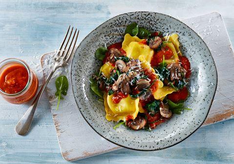 Ravioli med tomatsauce på bund af spinat