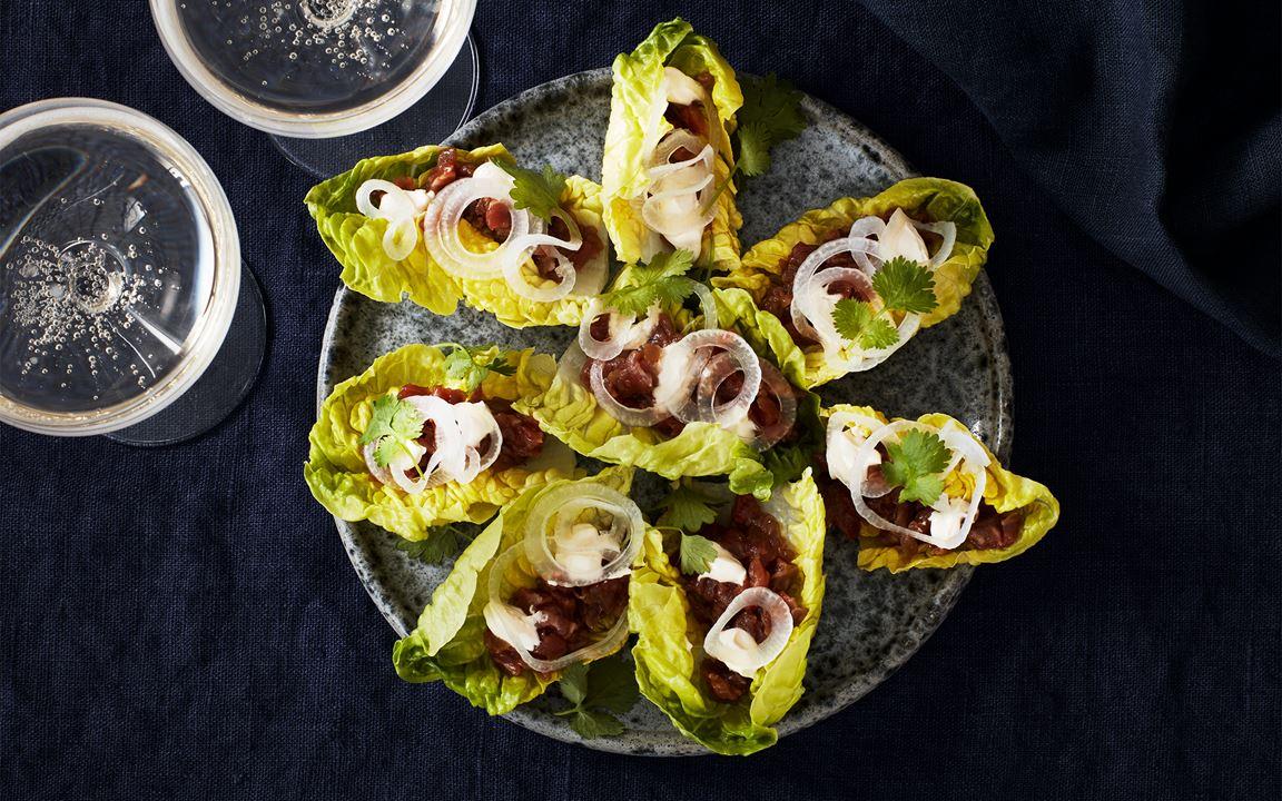 Oxfilétartar i salladsblad med picklad silverlök
