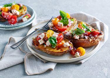 Bakad potatis med vitost, tomater och basilika
