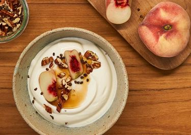 Arla Skyr Creamy with peach, pecan nuts, maple syrup and cardamom