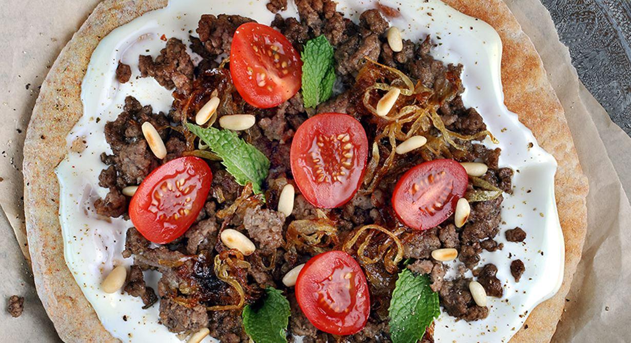 الخبز العربي مع جبنة كريم، اللحم المفروم، البصل المقلي، الطماطم والنعناع