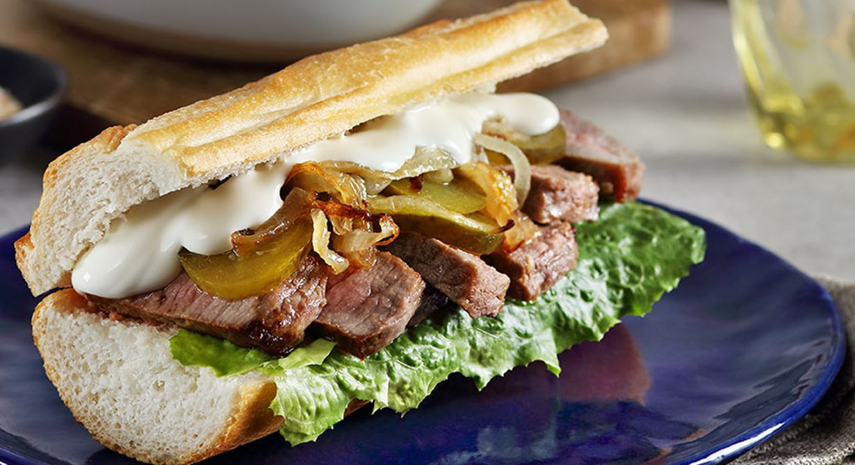 Baguette with steak, pickles and caramelized onions