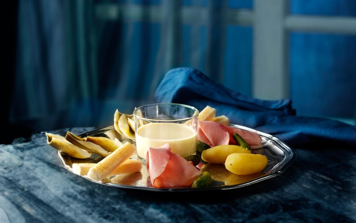 Cheese fondue with artichokes, smoked ham and gherkins