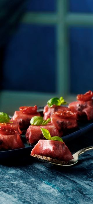 Small bresaola packages with cheese and olives
