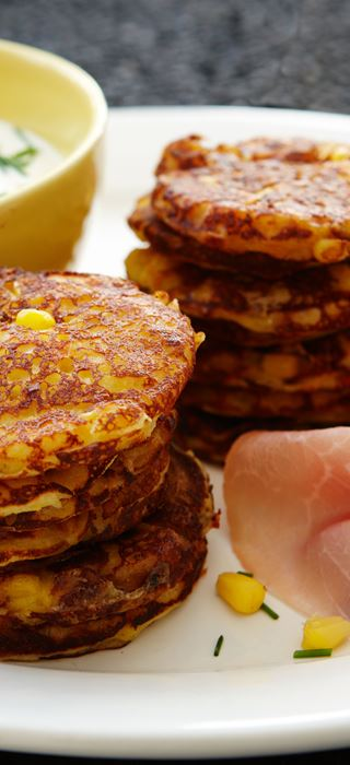 Fresh corn pancakes with ham and chive dressing