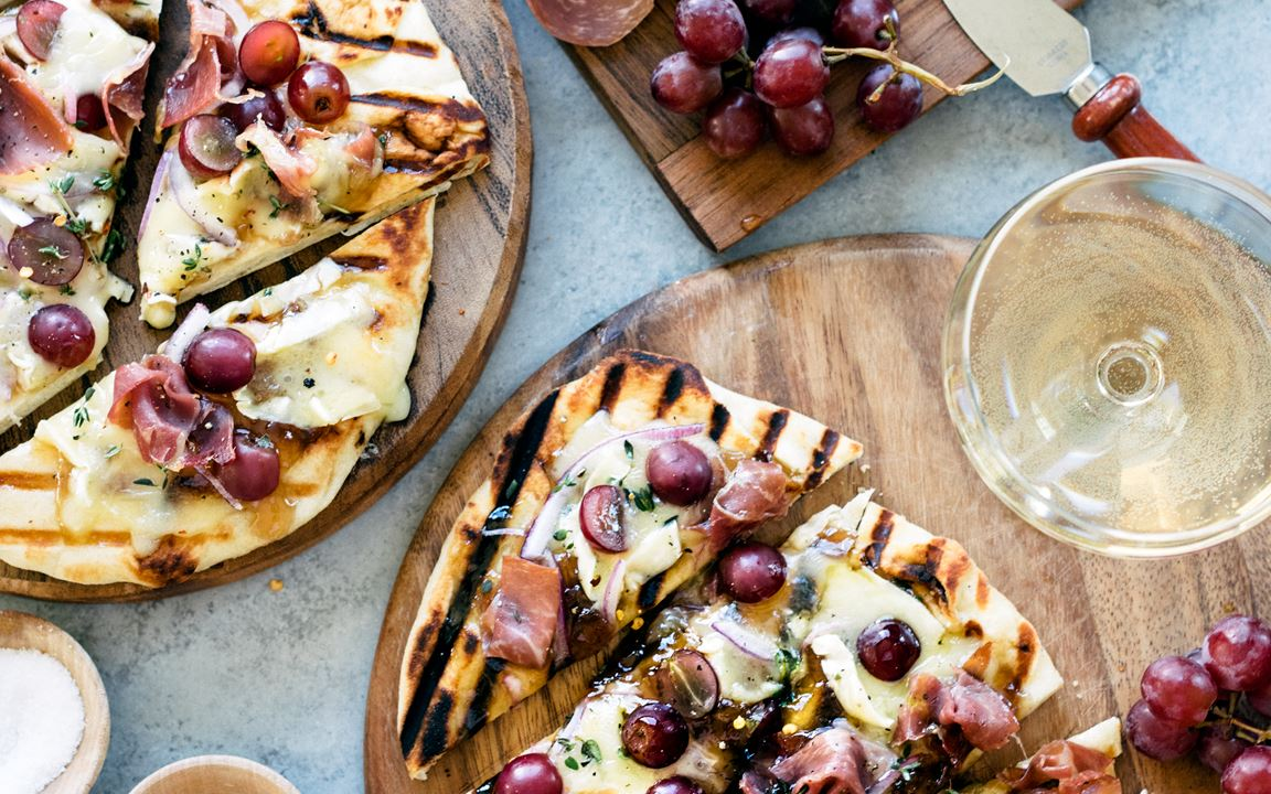 Grilled naan flatbread with grapes, onion jam, prosciutto and Double Creme Cheese
