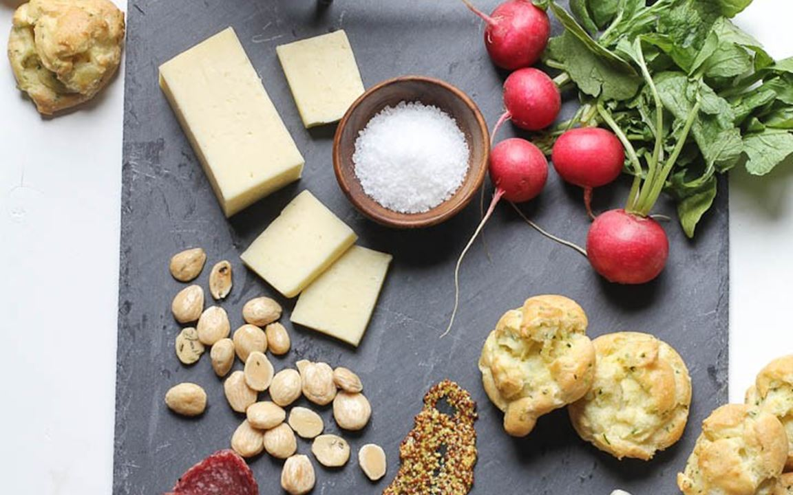 Spring cheese board with herb and pickled ramp gougeres