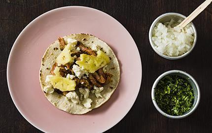 Tacos al pastor finns i vartenda gatuhörn i Mexiko och är lite av en nationalrätt. Det grillade köttet skärs tunt ner från ett kebabspett. Thomas toppar sin al pastor med ananas och smulad Apetina.
