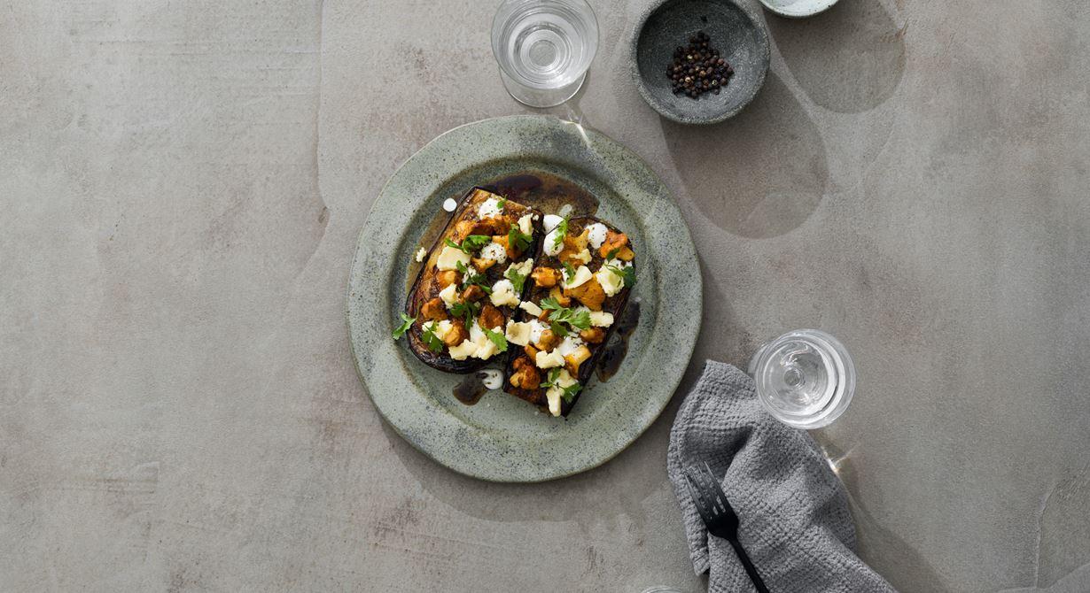Mjukt ugnsgratinerad aubergine med milt smörstekta kantareller, sval lavendelyoghurt och riven cheddar möter het tellicherrypeppar, kryddig spiskummin och färsk koriander.