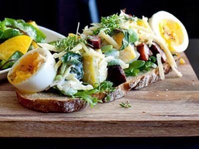 En rustik Grand Sandwich med mer pålägg än bröd. I botten en tunn skiva tyskt surdegsbröd. Bygg på med härliga kontraster av krämigt ägg och salt knaprigt fläsk  blandat med söt beta och syrlig gräddfil. Toppa med smakrik ost och kryddig krasse.