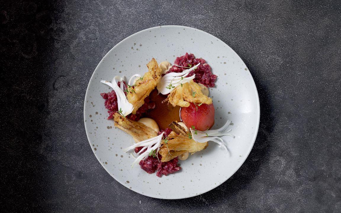 Ett mästerligt samspel. Mjuk tartar, rå, krispig och frasigt tempurafriterad lök ihop med picklade tomater. Inuti döljer sig sotad avokado som ger en grillad smak.