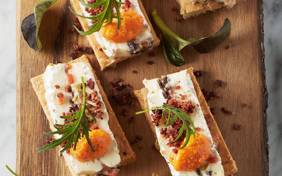 En ost-petit-four med äkta brie på frasig smördeg i smakrikt sällskap av oliver, pimentopuré och rostat sidfläsk. Lätt att förbereda och ha i kylen.