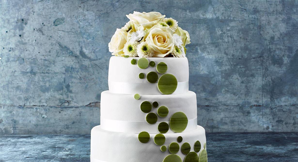 En bröllopstårta av högsta klass med somriga smaker och enkla, stilrena dekorationer. Moussetårtorna i tre våningar är klädda med tunn vit marsipan och har en frisk interiör av citroncurd och sötsyrlig jordgubbsgelé.