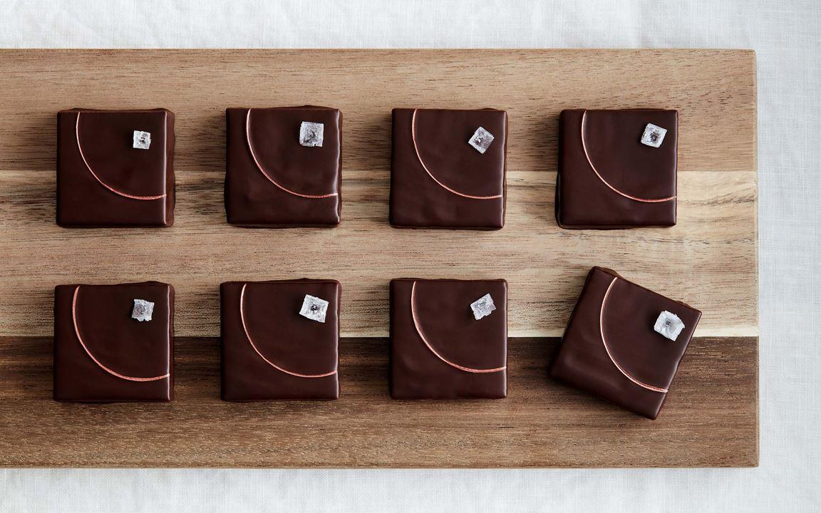 Ett hantverk av högsta klass. Hatten av för Kalles underbara petit-fourer förtrollade till flugsvampar med en ljuvlig ganache på hasselnötspraliné och hasselnötslikör. Foten är en saftig kaka doppad i citronjuice och vit choklad. Kakaonibs ger krisp och smak.