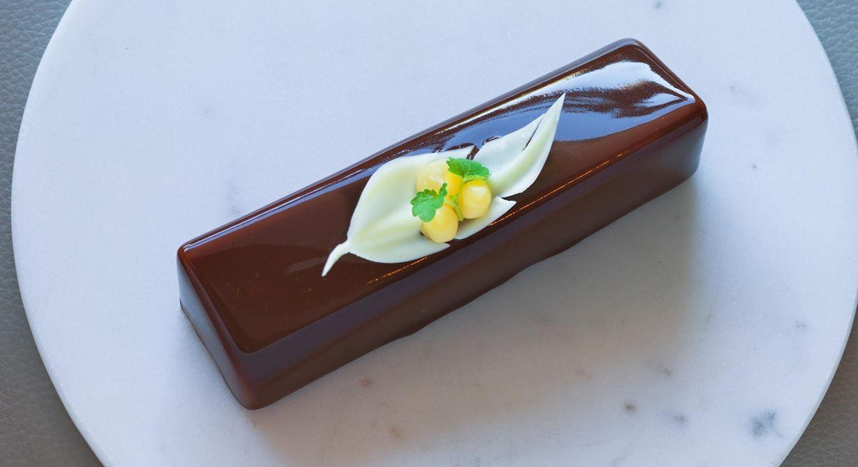 En dröm för alla chokladälskare. Krämig, silkeslen chokladmousse med syrlig calamansicrème, krisp från karamelliserade kakaonibs och seg browniebotten.  Högsta glansighet och syrlig ton i eftersmaken.