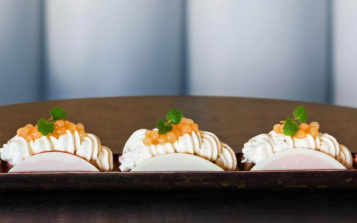 En försvinnande god munsbit med välbalanserade smaker och texturer. Söt choklad, syrlig aprikos, krämig vaniljgrädde och krispig, smörbrynt mandelmassa. En  storsäljare toppad med smakfulla tapiokapärlor.