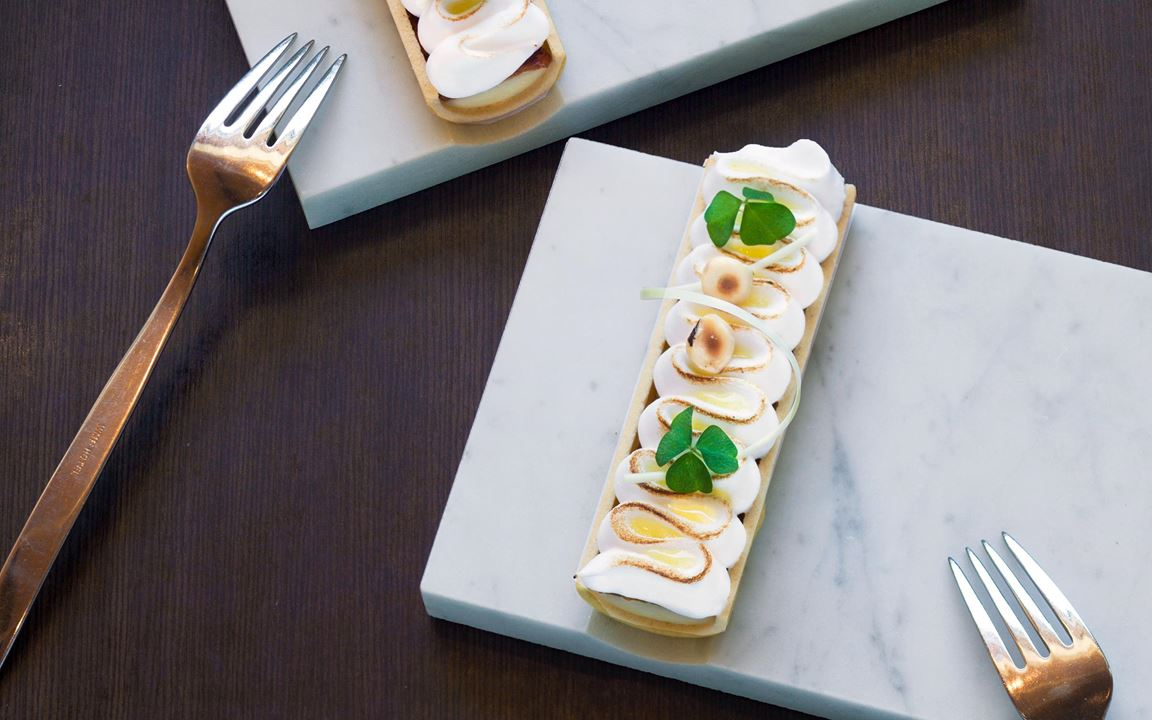 En klassiker i ny design. I perfekta mördegsskal ligger en smakrik citroncrème med krispig nougat inbäddad i italiensk maräng. Droppar av syrlig yuzugelé och rostade  hasselnötter blir som smycken ovanpå.
