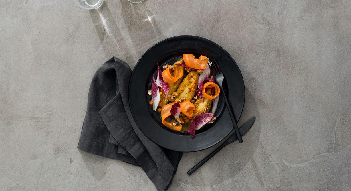 Smörstekt endive med apelsinlag smaksatt med havtorn och kittlande sanchopeppar. Dekorerad med röd endive och hyvlad morot. Pricken över i är de rostade valnötterna och valnötsdressingen som ringlas över salladen.
