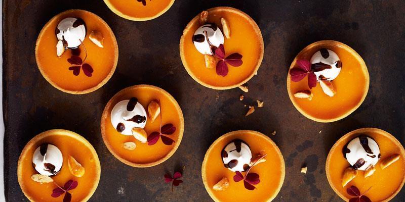 Smakfulla tarteletter fyllda med syrlig havtornscurd, fint dekorerade med söt lakritsmaräng, karamelliserade mandlar och oxalis.