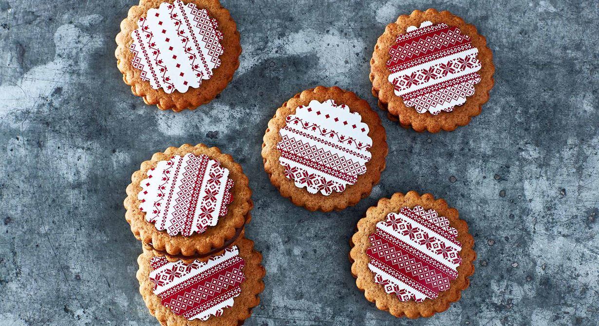 Uppmärksamma pepparkakan med en bodyr i choklad. Spritsa en kryddad chokladtryffel mellan två pepparkakor och lägg en julig schablon i choklad på den översta. Fina att säljas i cellofanpåse till advent och jul.