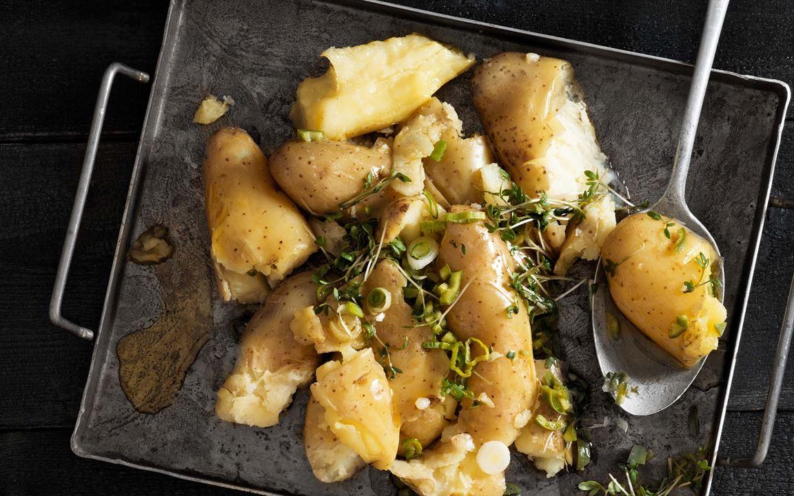 Krossa kokt potatis och rosta den härligt frasig i ugn. Har du kokt potatis över så går det också bra. Toppa med en het, syrlig citronvinägrett med grön chili som ger extra smakskjuts och fräschör.