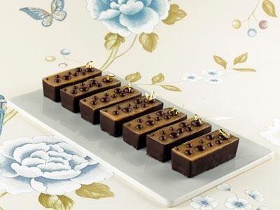 Krämig och len kolafudge på valnötsbotten med chokladprickar och bladguld som ger en modern, lite ostrukturerad dekor.