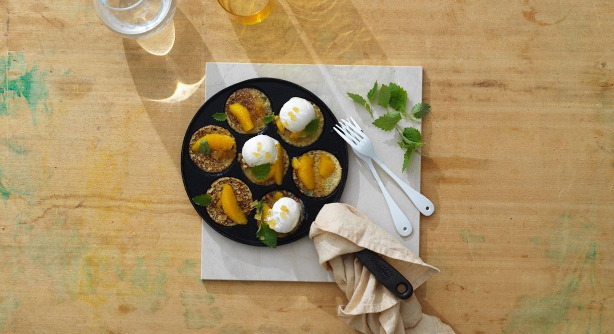 """Med inspiration från av den franska klassikern """"Crêpes Suzette"""" serveras dessa Grand Marnier-flamberade plättar med varma apelsinfiléer, syltad ingefära och vaniljglass."""