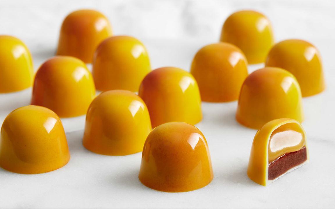 De gyllene, glansiga pralinerna fyllda med kanelganache och mandarinkaramell är helt oemotståndliga. De är fint sprejade så att färgen skiftar och den ena sidan blir något mörkare. Konjaken i karamellen bara anas och ger en djupare smak ihop med kanelens mjuka ton.