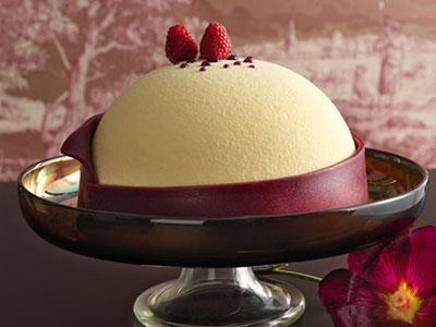 Ny design med vit choklad- och vaniljbavaroise, hallonjelly och en krispig mandelbotten som döljs av marsipan. Tårtan är sprayad med vit choklad.