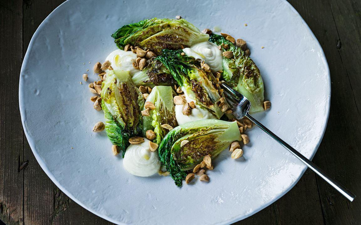En tillagad sallad med härliga konsistenser av mjukt och knaprigt. Sallad är en perfekt grönsak att smörsteka eftersom den suger åt sig andra smaker så bra. Grymt gott med den aioliliknande vitlöksemulsionen och de rostade mandlarna.