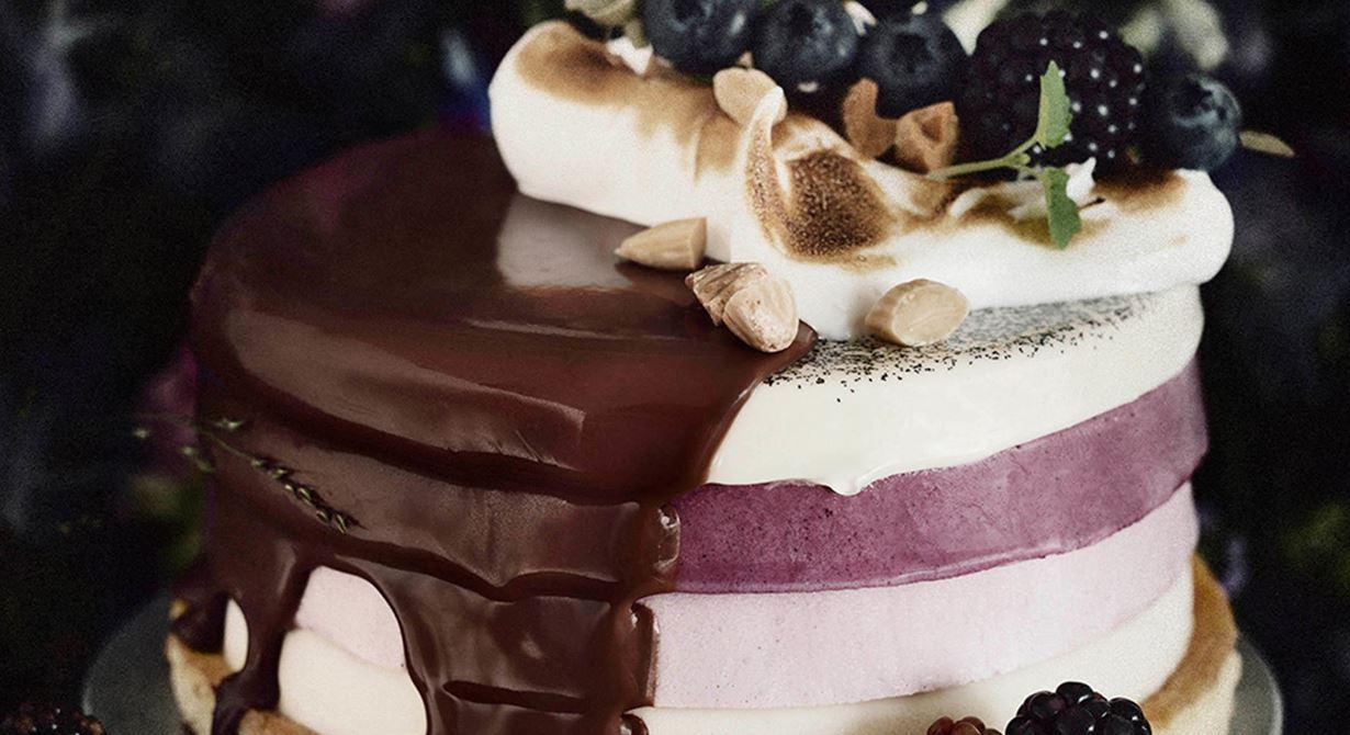 Blåbärsmousse med vaniljpannacotta och björnbärsmousse kröns av saltrostad mandel, italiensk maräng och en mjölkchokladglaze.