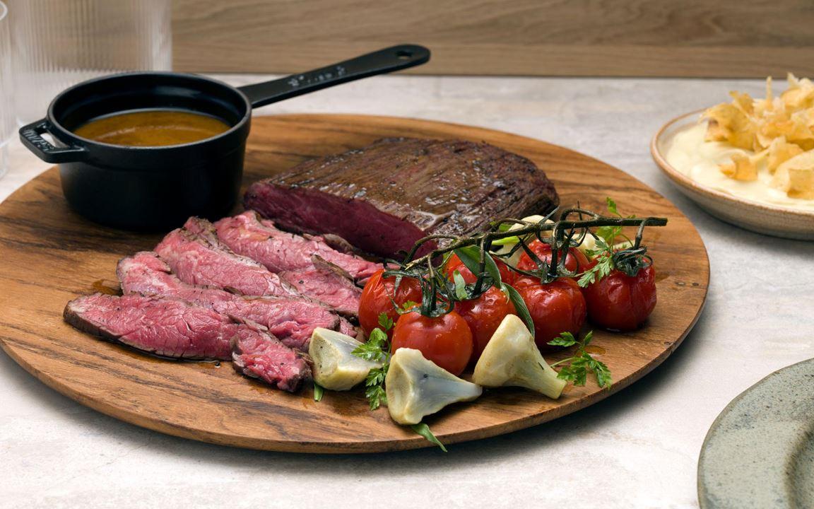 Sotad flankstek med kronärtskocka, bakade tomater och örtig steksky