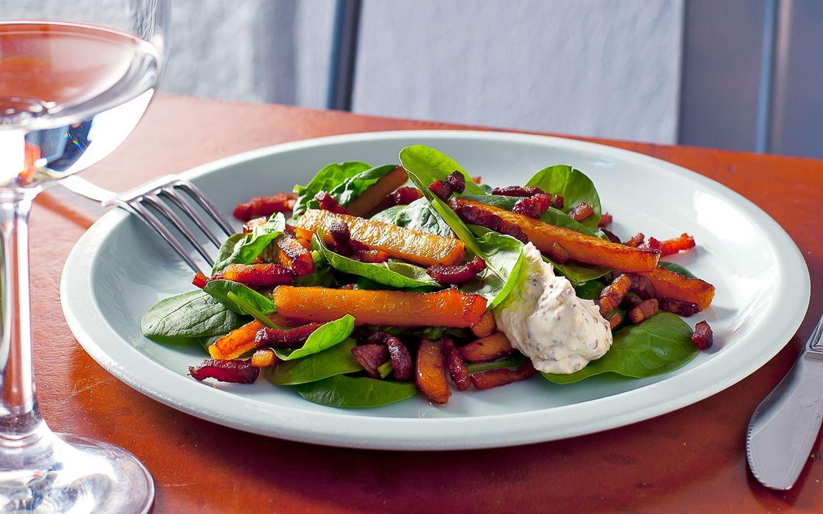 Kålrot är en billig och underskattad råvara. Den är söt, matig och blir god ljummen i en sallad med bacon. Matcha med en krämig dressing på två sorters senap.