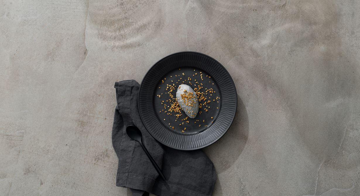 Denna eleganta vuxna glass är gjord på svarta sesamfrön och smaksatt med sanchopeppar. Glassen serveras toppad med karamelliserade sesamfrön.