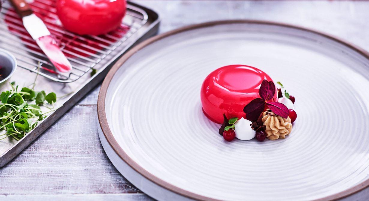 En dessert som passar vid större sällskap och event. Tranbärsbakelsen tas ur frysen någon timme före servering och glaseras direkt. Dekorera med övriga komponenter och ställ i kyl fram till servering.