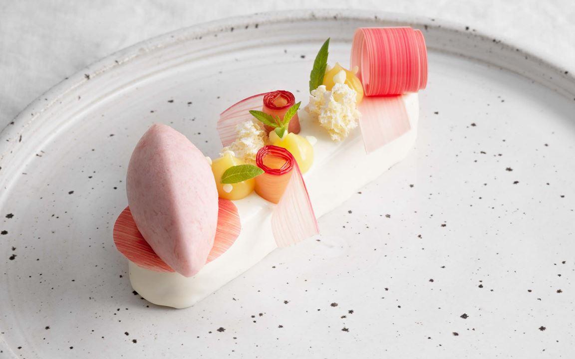 Ett smakminne från Kalles barndom och en somrig dessert med rabarber i olika kompositioner. En imponerande helhet med olika texturer, smaker och fina dekorationer. De spegelblanka chokladbanden som skiftar i rosa är förvillande lika band av hyvlad rabarber.